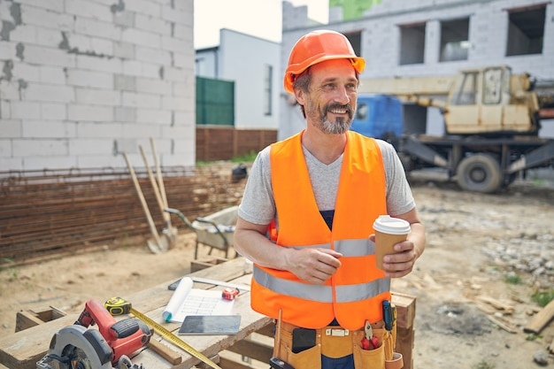 Улыбающийся зрелый строитель, держащий одноразовый бумажный стаканчик с крышкой