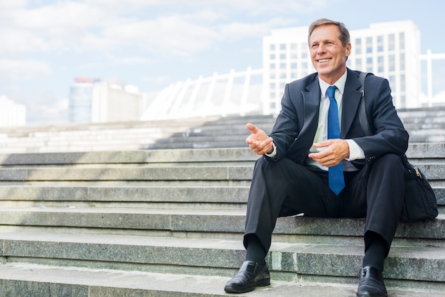 Smiling mature businessman making hand gesture sitting on staircase