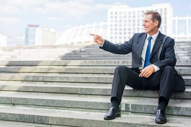 Smiling mature businessman pointing at something while sitting on staircase