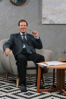 柔らかいアームチェアに座る笑顔の成熟したビジネスマン