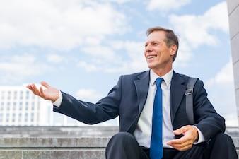 手のジェスチャーを作る階段に座って笑顔の成熟したビジネスマン
