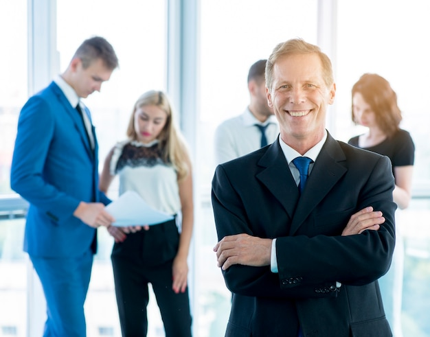 Smiling mature businessman standing in front of his colleagues at workplace