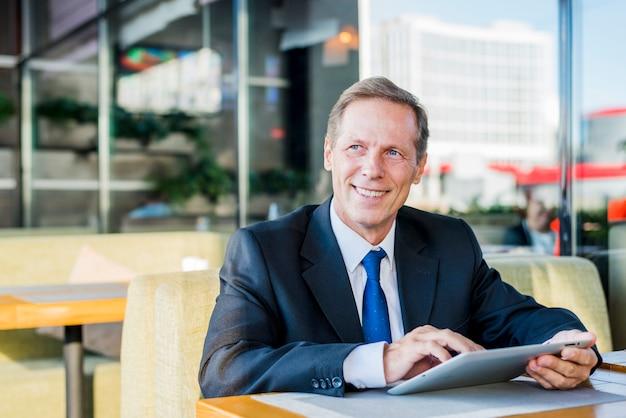 Smiling mature businessman using digital tablet in caf�