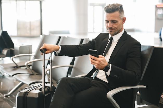 携帯電話を使用して笑顔の成熟した実業家
