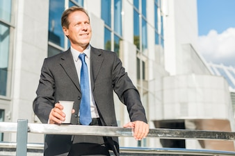 Smiling mature businessman with cup of coffee standing at outdoors