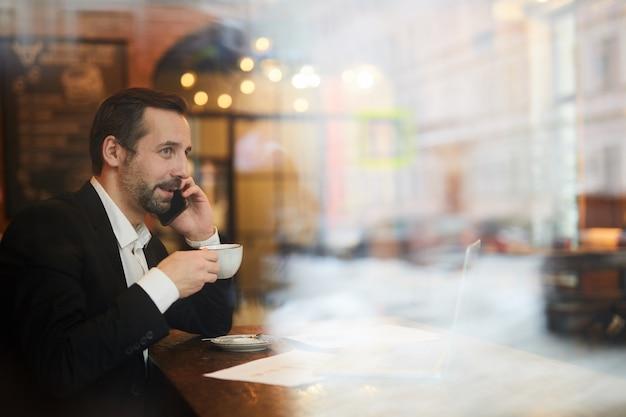 Улыбающийся зрелый бизнесмен работает в кафе
