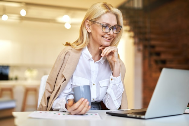 Smiling mature businesswoman in glasses using laptop and drinking coffee while doing some paperwork