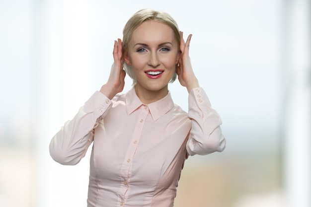 Smiling mature businesswoman is doing her hair