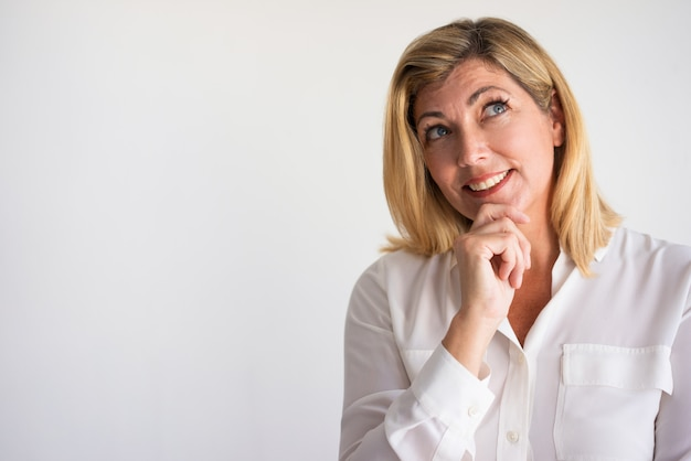 Smiling mature caucasian woman leaning chin on hand and looking up in happy thoughts.