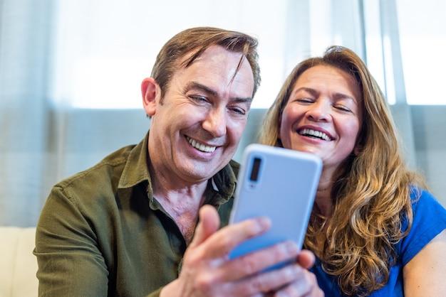 モバイルで何か面白いものを見ている自宅で成熟したカップルの笑顔。高品質の写真