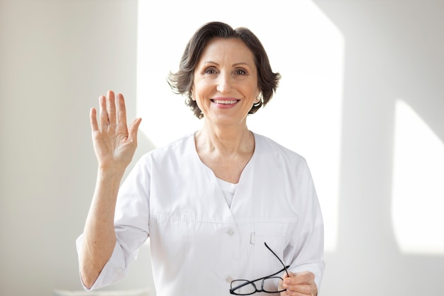 Smiling mature female doctor therapist looking at camera. professional medical worker holding video call consultation with a patient online