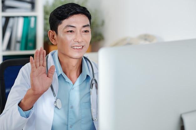 Улыбающийся зрелый врач общей практики машет рукой, приветствуя коллег на онлайн-конференции