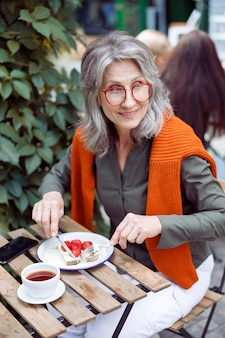 Smiling mature lady eats toast with cream and strawberries sitting at table on outdoors cafe terrace