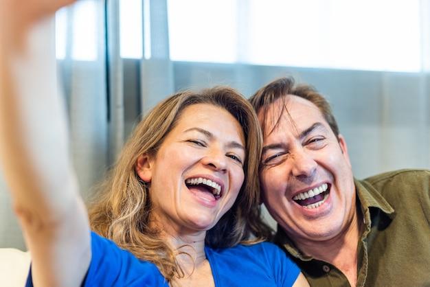 Улыбающийся зрелый мужчина и женщина, делающие селфи. фото высокого качества