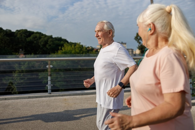 Улыбающиеся зрелые мужчина и женщина с хвостиком вместе бегают по пешеходному мосту в летний день