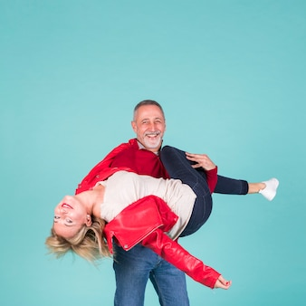 Smiling mature man carrying his wife against turquoise background