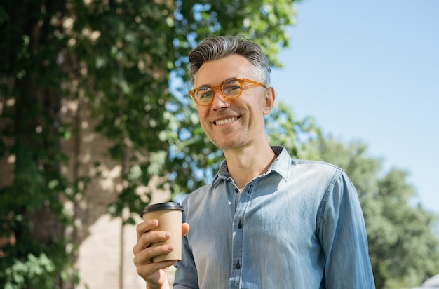 Smiling mature man drinking coffee outdoors