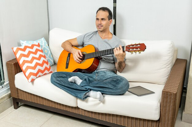 Улыбающийся зрелый мужчина играет на гитаре рядом с планшетом.