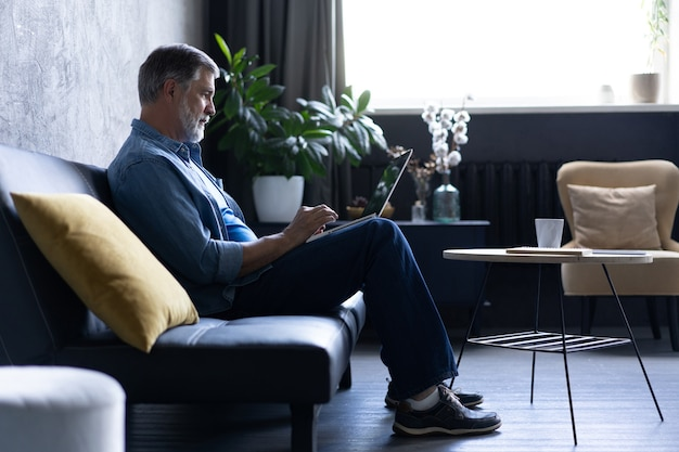 リビングルームのラップトップで入力してソファに座って笑顔の成熟した男。自宅で検疫の封鎖に取り組んでいます。社会的距離の自己隔離