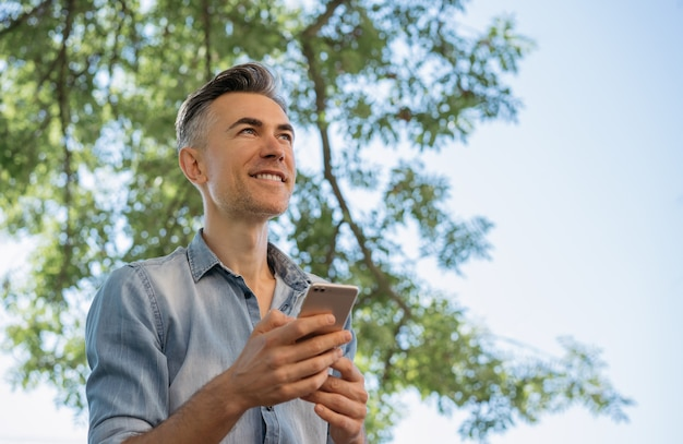 Smiling mature man using mobile phone, shopping online.
