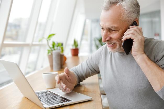 Улыбающийся зрелый мужчина работает с ноутбуком и разговаривает по мобильному телефону в кафе в помещении