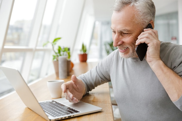 Smiling mature man working with laptop and talking on cellphone in cafe indoors