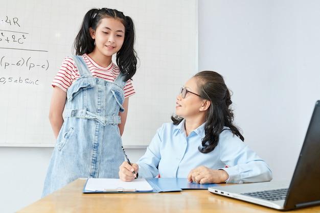 여 학생의 테스트 결과를 확인하는 성숙한 수학 교사 미소