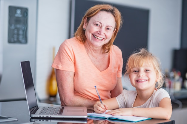 Smiling mature mother helps her daughter in preparing chores at home. online education concept.