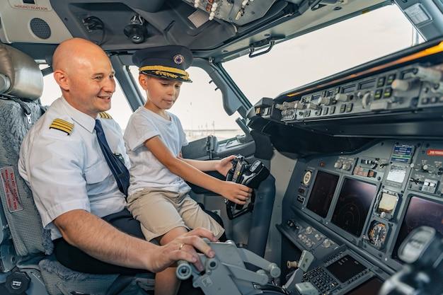 Улыбающийся зрелый пилот и ребенок, сидящие в кабине