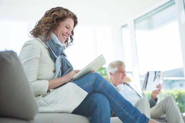 Улыбается зрелая женщина с помощью цифрового планшета
