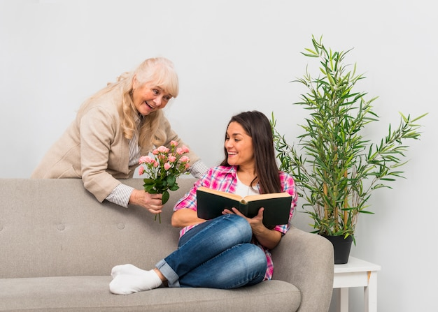 Smiling mature woman giving rose bouquet to her daughter reading book at home