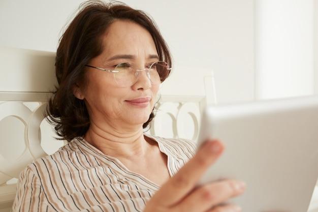 Sorridente donna matura in bicchieri utilizzando digital tablet pc sdraiata sul suo letto in una camera da letto