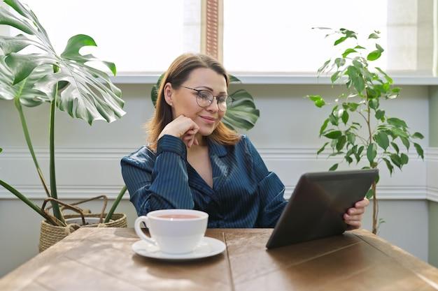 デジタルタブレットを読んでテーブルに座っているお茶とパジャマで自宅で朝食を食べている成熟した女性の笑顔。読んだメール、ニュースから幸せな女性。ポジティブな感情、情報、人生、40代の人々