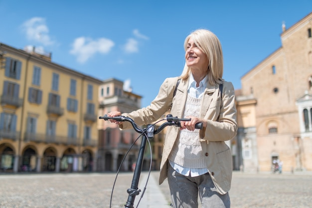 Smiling mature woman holding her bike in a big square, sunny day in european country