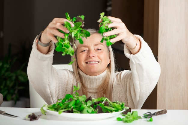 Улыбающаяся зрелая женщина держит полную горсть зеленого салата
