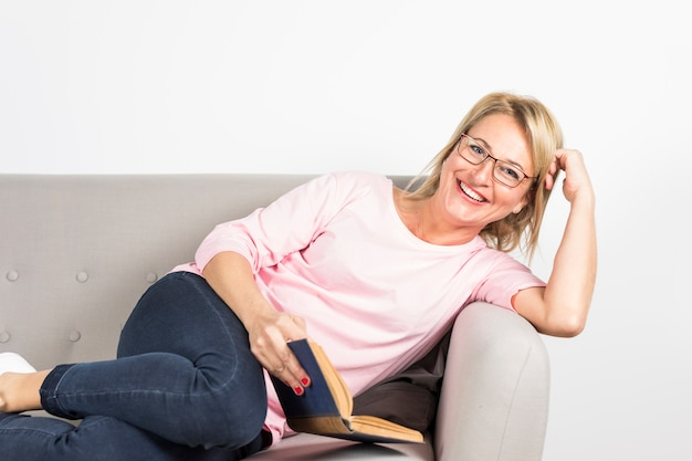 Smiling mature woman leaning on sofa holding book in hand against white backdrop