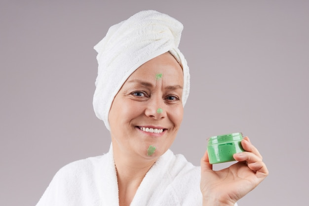 Smiling mature woman in a robe, white towel on her head, holding a jar of green fruit cream. facial skin care concept.  over gray wall.