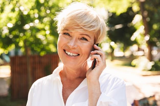 携帯電話で話している笑顔の成熟した女性