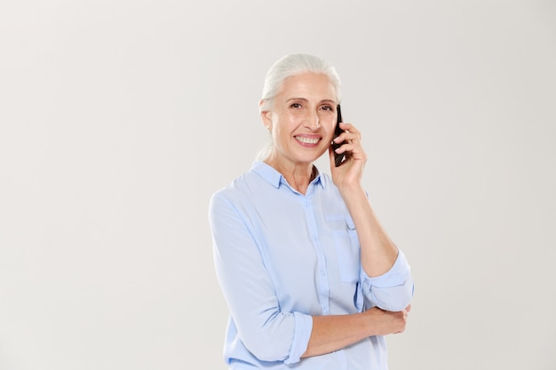 Smiling mature woman talking on smartphone isolated