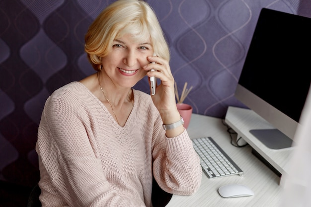 Smiling mature woman using mobile phone while working by computer at home