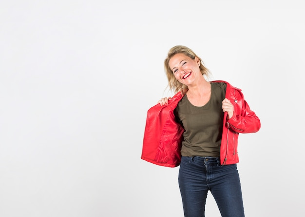 Smiling mature woman wearing red leather jacket standing against white backdrop