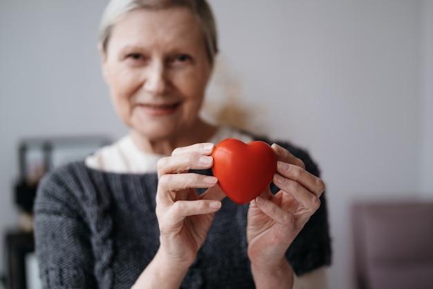 彼女の手に赤いハートと笑顔の成熟した女性
