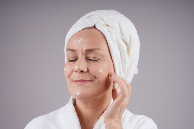 彼女の頭に白いタオルで笑顔の成熟した女性、彼女の顔にクリームを適用し、彼女の目を閉じます。フェイシャルケアのコンセプト。灰色の壁に隔離