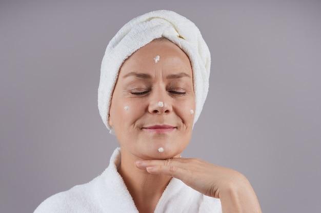 Улыбается зрелая женщина с белым полотенцем на голове, нанося крем на лицо, закрывая глаза. концепция ухода за лицом. изолировать на серой стене