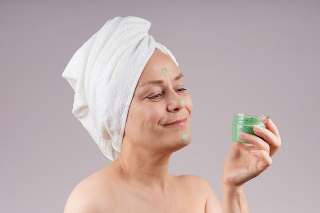 緑のフルーツクリームの瓶を持って、彼女の頭に白いタオル、裸の肩を持つ笑顔の成熟した女性。フェイシャルスキンケアのコンセプト。灰色の壁を越えて。