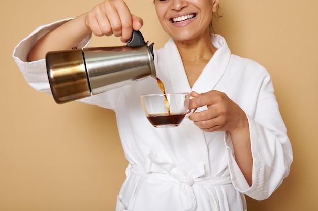 間欠泉のコーヒーメーカーからガラスのカップにコーヒー飲料を注ぐ白いバスローブで歯を見せる笑顔で成熟した女性を笑顔。テキスト用のスペースとベージュの表面上の孤立した肖像画