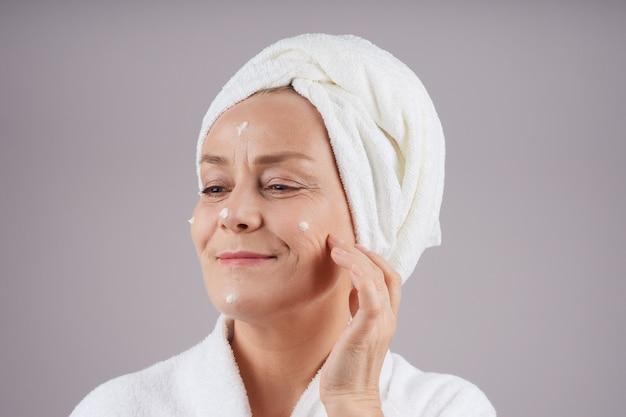 彼女の顔にクリームを適用する彼女の頭に白いタオルで笑顔の成熟した女性。フェイシャルケアのコンセプト。灰色の壁に隔離