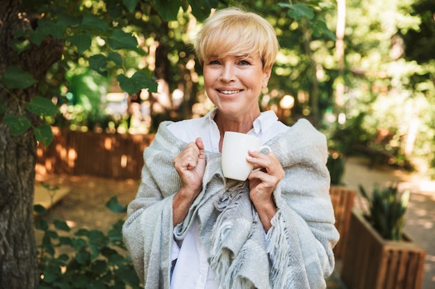 毛布に包まれた笑顔の成熟した女性