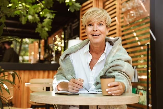 Улыбаясь зрелая женщина, писать в тетради