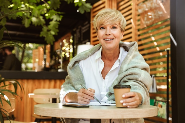 Smiling mature woman writing in a notebook